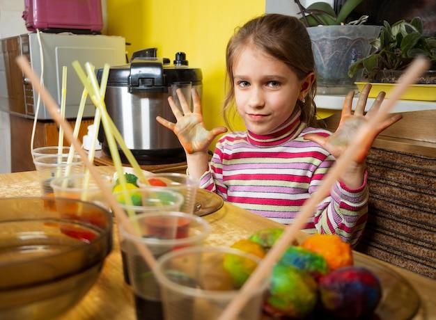 Nahaufnahme von händen von kindern, die farbe und malerei auf weißen gekochten eiern verwenden, während sie sich auf ostern vorbereiten