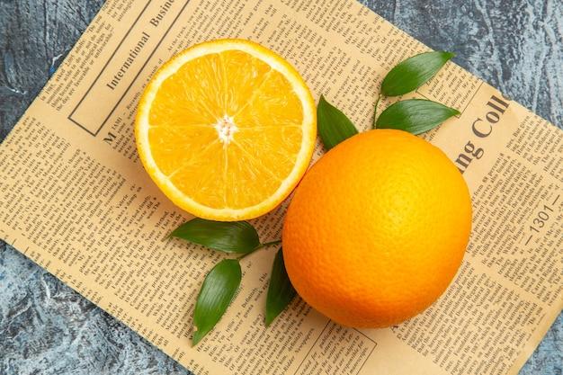 Nahaufnahme von halbierten und ganzen frischen orangen mit blättern auf zeitung auf grauem hintergrund stockfoto