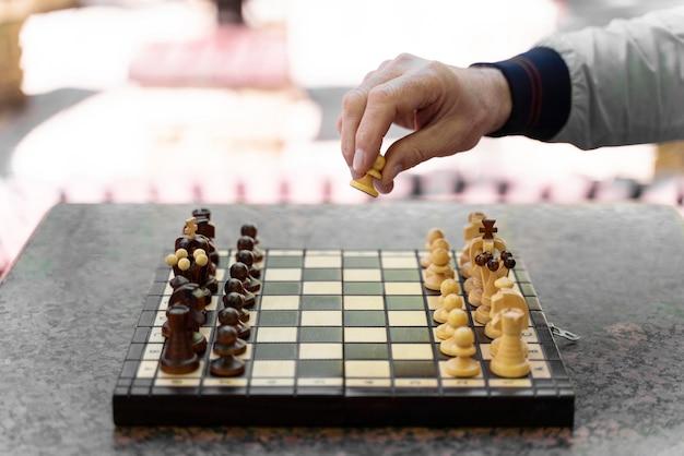 Nahaufnahme von hand bewegte schachfigur