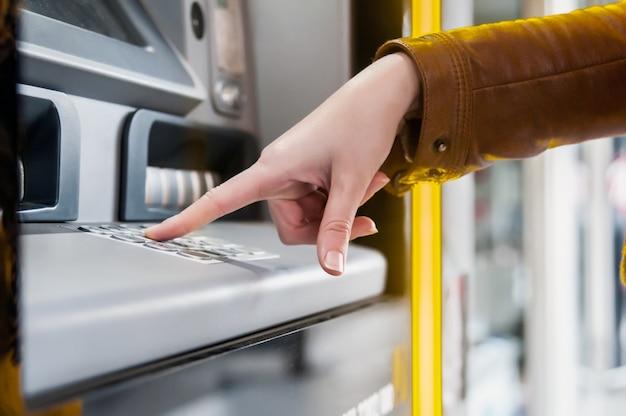 Nahaufnahme von hand eingabe pin an einem geldautomaten. finger, um einen pin-code auf einem pad zu drücken. sicherheitscode auf einem geldautomaten. weibliche arme, atm - einstiegstift