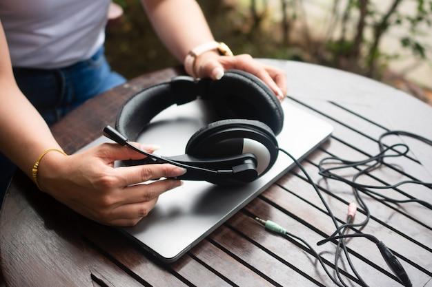 Nahaufnahme von hand halten kopfhörer und computerarbeit callcenter-unterstützung