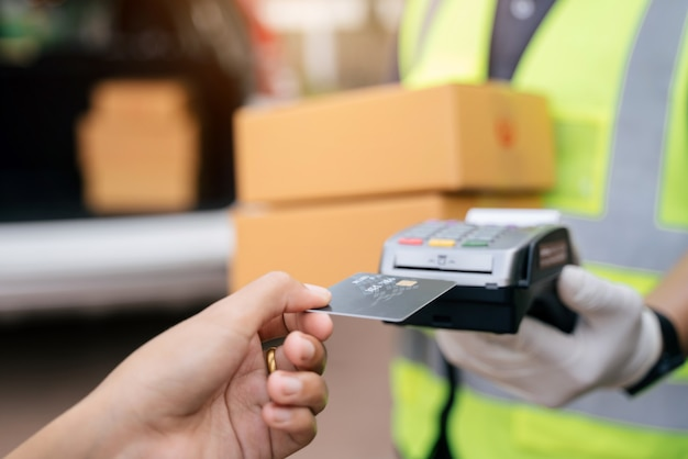 Nahaufnahme von hand lieferung mann mit kreditkarte swiping-maschine zu bezahlen. hand mit kreditkarte durch das terminal für die zahlung außerhalb des lagers streichen, fokuskreditkarte auswählen.