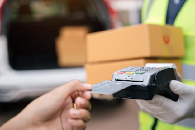 Nahaufnahme von hand lieferung mann mit kreditkarte swiping-maschine zu bezahlen. hand mit kreditkarte durch das terminal für die zahlung außerhalb des lagers streichen.