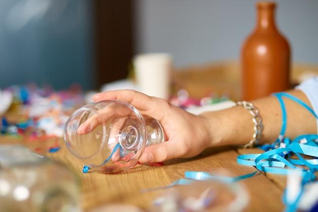 Nahaufnahme von hand mann hält ein glas brandy und schläft am tisch in einem unordentlichen zimmer nach junggesellenabschied