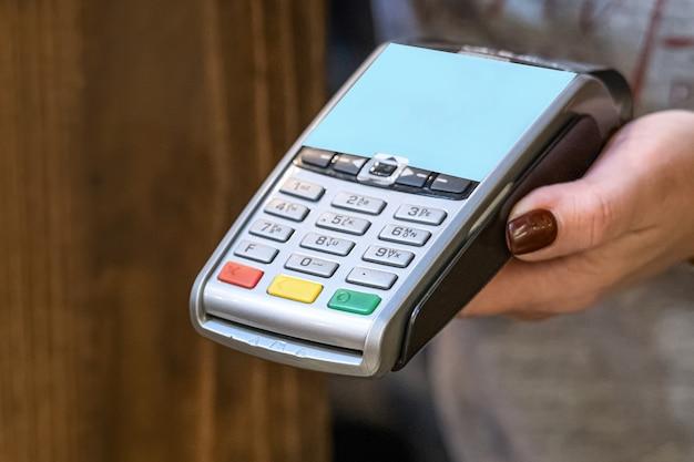 Nahaufnahme von hand mit kreditkarte swiping-maschine zu bezahlen. hand mit kreditkarte zum bezahlen in der cafeteria durch das terminal streichen. mann, der kreditkartencode in swipe-maschine eingibt.