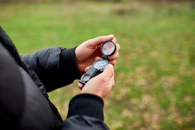 Nahaufnahme von hand reisender mit kompass auf natur, reisekonzept, campingausflug, gps, orientierungslauf, navigator