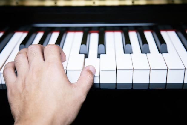 Nahaufnahme von handmenschenmannmusiker, der klaviertastatur mit selektiven fokustasten spielt.