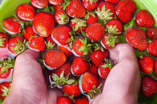 Nahaufnahme von handwascherdbeeren in grüner tasse