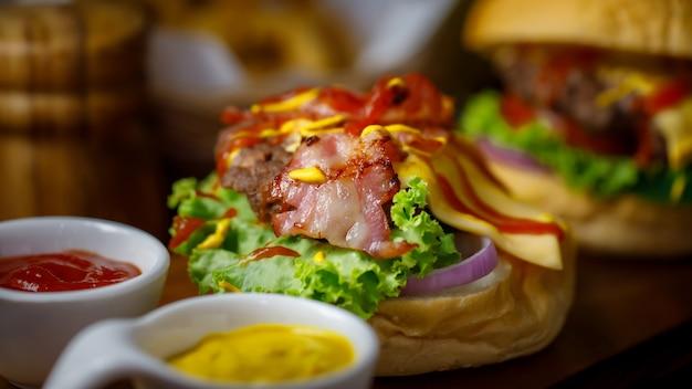Nahaufnahme von hausgemachtem hamburger mit sauce und speck auf holzplatte mit dunklem licht.
