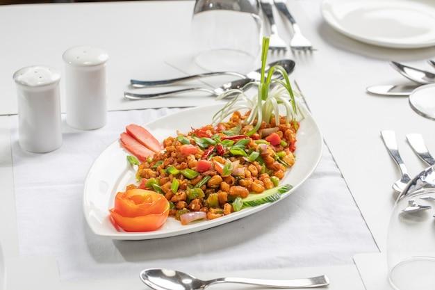 Nahaufnahme von hausgemachtem vegetarischem mexikanischen streetfood-feldsalat mit koriander, limette, mayonnaise, knoblauch, chili und käse auf weißem teller