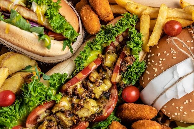 Nahaufnahme von hausgemachten leckeren burger und hot dogs mit pommes frites mit gebratenem hühnchen. traditionelles amerikanisches essen. fastfood