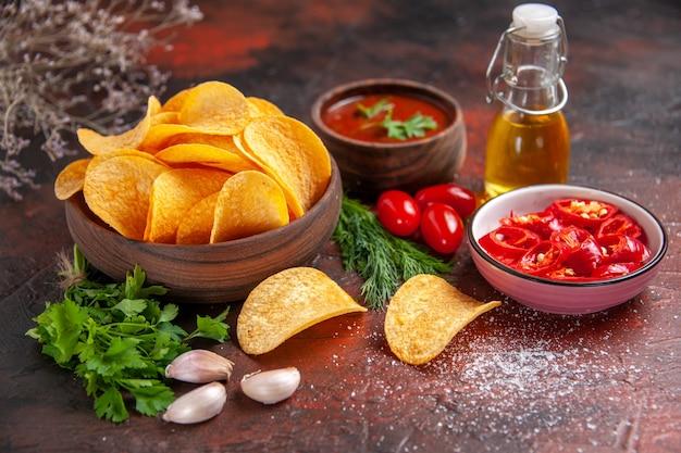 Nahaufnahme von hausgemachten leckeren knusprigen kartoffelchips in einer kleinen braunen schüssel kartoffeln ölflasche grüne tomaten knoblauchketchup und gehackter pfeffer auf dunklem tisch