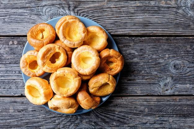 Nahaufnahme von hausgemachten yorkshire-puddings auf einer platte auf einem rustikalen holztisch, englische küche, ansicht von oben, flatlay, freier raum