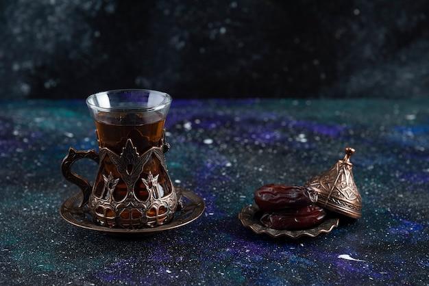Nahaufnahme von heißem tee und trockenem datum auf blauer oberfläche