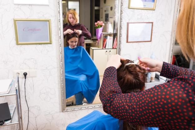 Nahaufnahme von hinten auf die stylistin, die das haar eines jungen brünetten kunden im salon mit unscharfer reflexion im großen ganzkörperspiegel stylt
