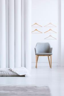 Nahaufnahme von holzbügeln über einem einfachen grauen sessel in einer open-space-wohnung mit wohnzimmer und schlafzimmer