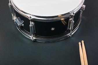Nahaufnahme von hölzernen Trommelstöcken und von Trommel auf schwarzem Hintergrund