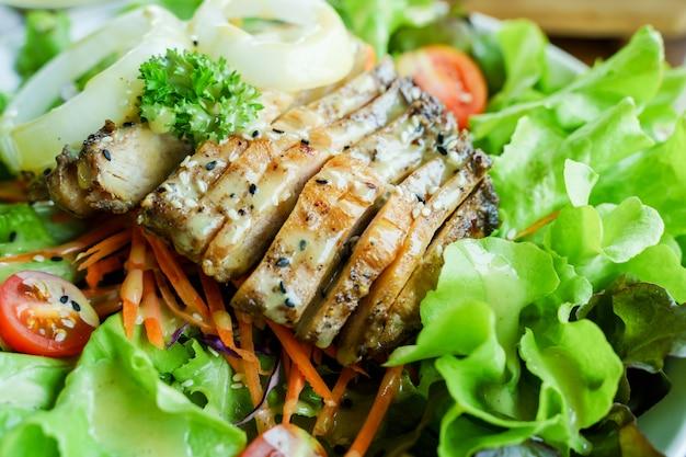 Nahaufnahme von hühnersalat mit tomaten, zwiebeln und salat.