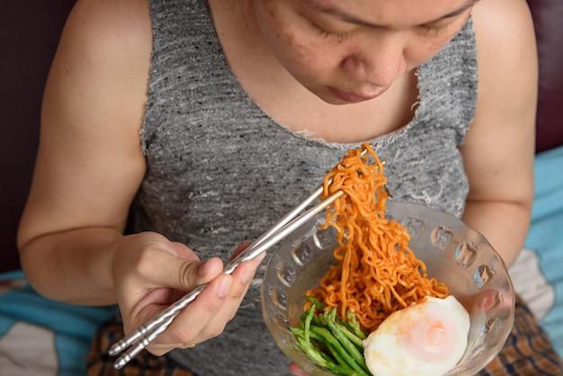 Nahaufnahme von hungrigen asiatischen frauen essen nudeln zu hausen