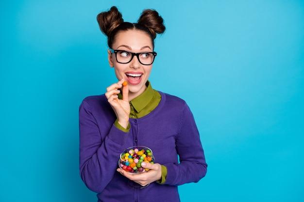 Nahaufnahme von ihr, sie ist ein hübsches, hübsches, hübsches, hungriges, fröhliches, fröhliches mädchen, das es genießt, karamellbonbons zu essen, isoliert auf hell leuchtendem, lebendigem blaugrünem türkisfarbenem hintergrund