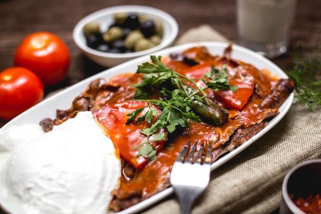 Nahaufnahme von iskender kebab, garniert mit tomate und petersilie, serviert mit joghurt