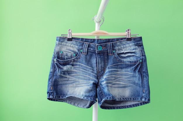 Nahaufnahme von jeans-shorts in einem kleiderbügel isoliert auf grünem hintergrund