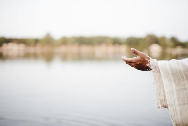 Nahaufnahme von jesus christus, der eine hand um hilfe reicht