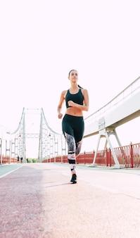 Nahaufnahme von joggen schöne brünette sportliche frau in cooler kleidung