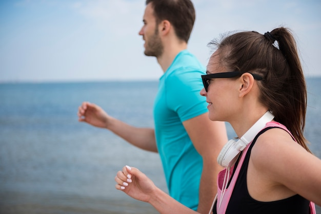 Nahaufnahme von jungen fitten leuten, die durch das meer joggen