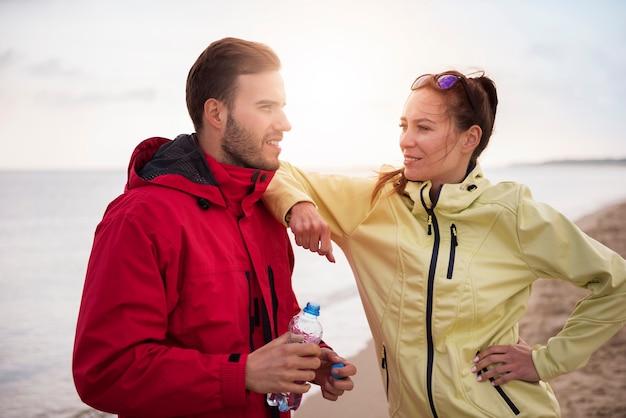 Nahaufnahme von jungen fitten leuten, die durch das meer joggen Kostenlose Fotos