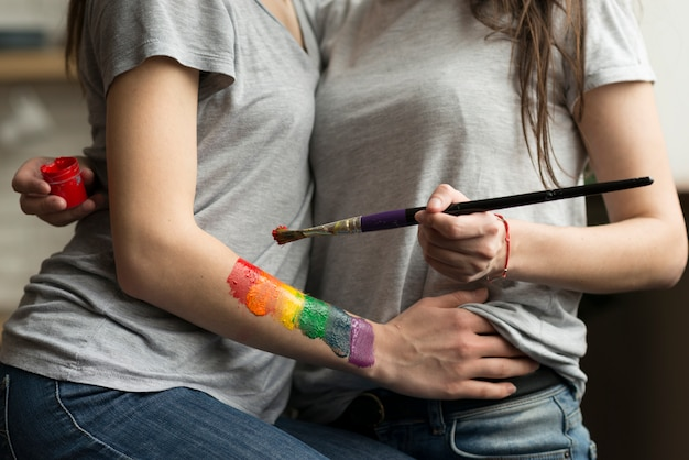Nahaufnahme von jungen lesbischen paaren mit malerpinsel und acrylfarbe