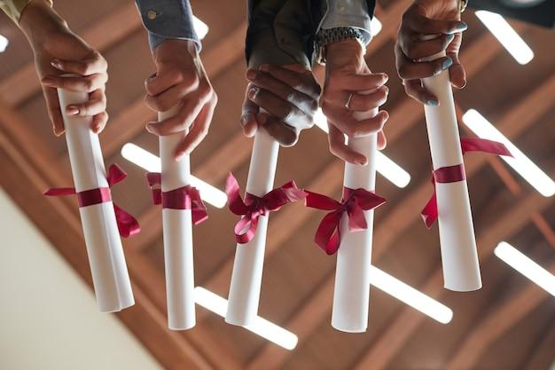 Nahaufnahme von jungen leuten, die diplome mit rotem band während der abschlussfeier im college halten, kopienraum
