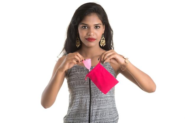 Nahaufnahme von jungen mädchenhänden, die menstruationstasse halten, gynäkologie-konzept, zeige daumen hoch, die die verwendung der menstruationstasse genehmigen