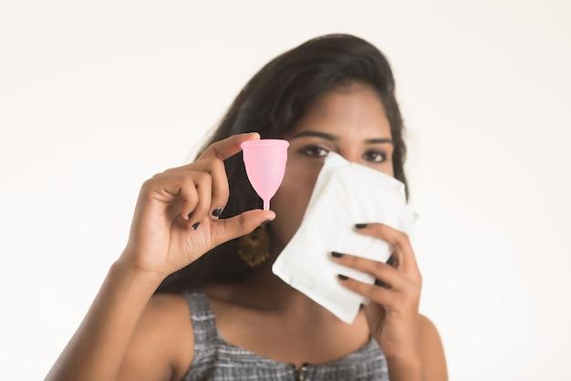 Nahaufnahme von jungen mädchenhänden, die menstruationstasse halten, gynäkologisches konzept, zeige daumen hoch, die die verwendung der menstruationstasse genehmigen
