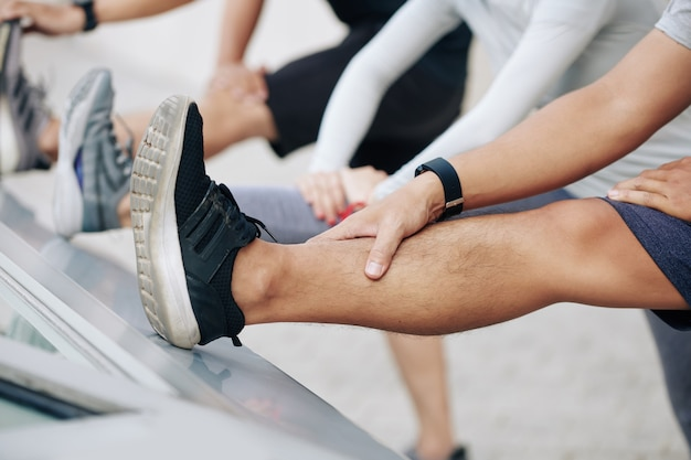 Nahaufnahme von jungen männern, die sich zu gerade angehobenen beinen nach vorne beugen und versuchen, die zehen zu berühren