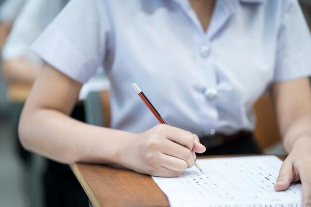 Nahaufnahme von jungen studenten konzentrieren sich auf die prüfung im klassenzimmer. studentin schreibt auf dem prüfungsantwortpapier im klassenzimmer.