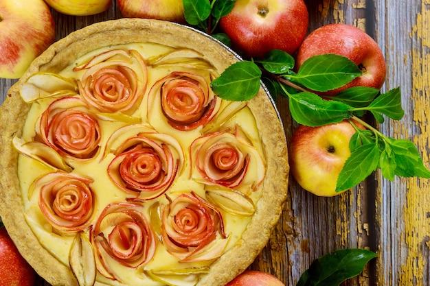 Nahaufnahme von käsekuchen mit rosenform apfel dekoriert und frischen äpfeln. draufsicht.
