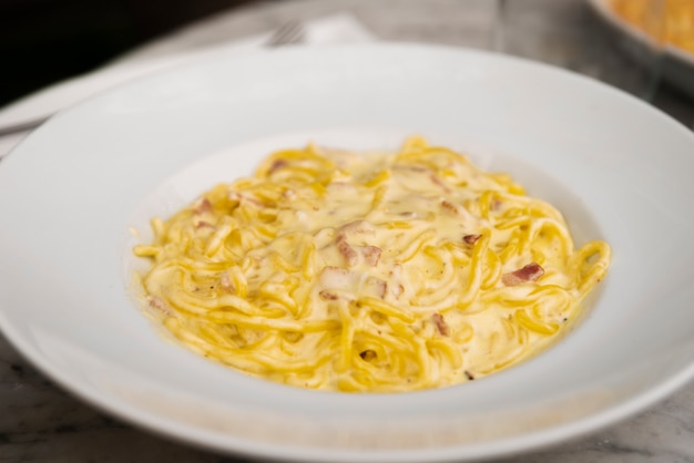 Nahaufnahme von käsigen spaghettiteigwaren in der weißen keramischen platte