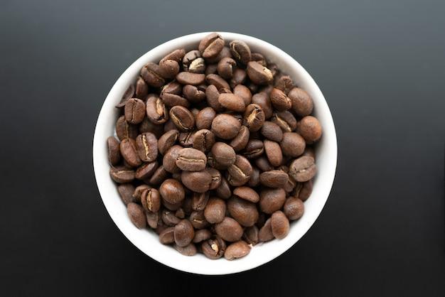 Nahaufnahme von kaffeebohnen in einer weißen schüssel an einer schwarzen wand
