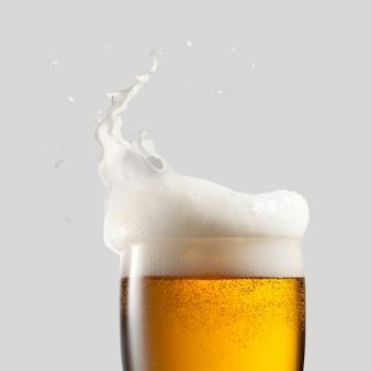Nahaufnahme von kaltem bier mit schaum und spritzer auf grauem hintergrund