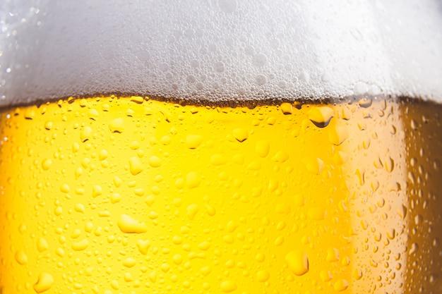 Nahaufnahme von kaltem bierglas mit schaum und tropfen. selektiver fokus.