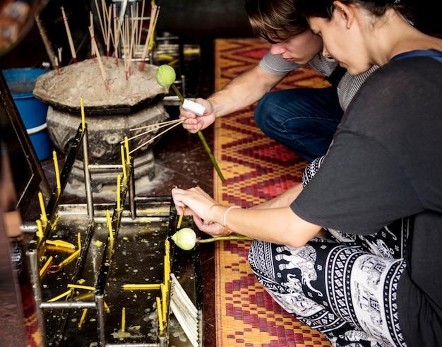 Nahaufnahme von kaukasischen paaren, die herauf die kerzen innerhalb des thailändischen tempels in bangkok leuchten
