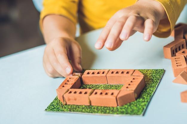Nahaufnahme von kinderhänden, die mit echten kleinen lehmziegeln am tisch spielen