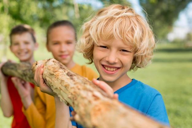 Nahaufnahme von kindern, die baumstamm zusammen tragen