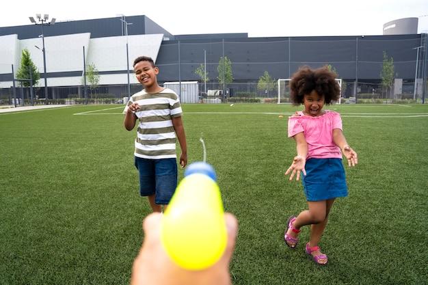 Nahaufnahme von kindern, die mit wasserpistole spielen