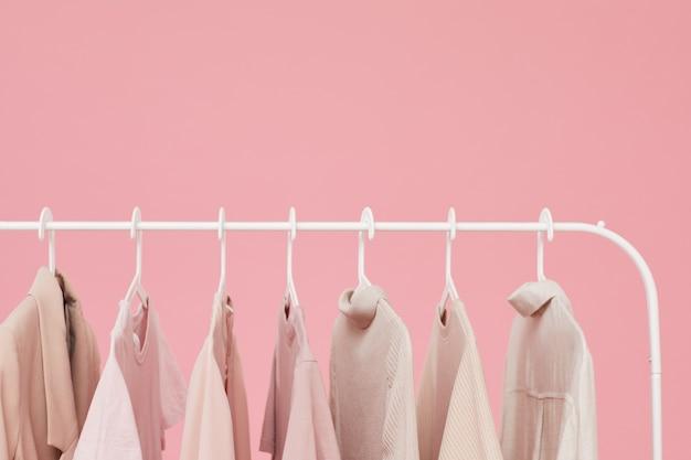 Nahaufnahme von kleidern und hemden, die auf dem gestell lokalisiert auf rosa hintergrund hängen