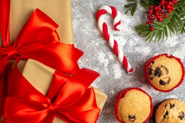 Nahaufnahme von kleinen cupcakes weihnachtsgeschenke mit rotem band auf eisfläche