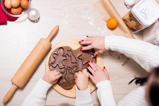 Nahaufnahme von kleinen mädchen und ihrer mutter, die weihnachtsplätzchen oder lebkuchen in der küche kochen