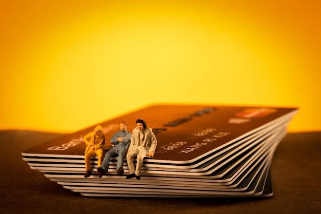 Nahaufnahme von kleinen personenfiguren, die auf einem stapel von kreditkarten sitzen