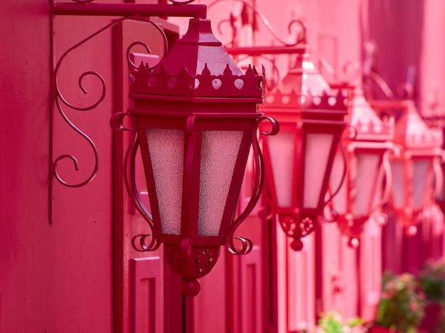 Nahaufnahme von kleinen straßenlaternen auf einer rosa wand. romantische rosa straße.